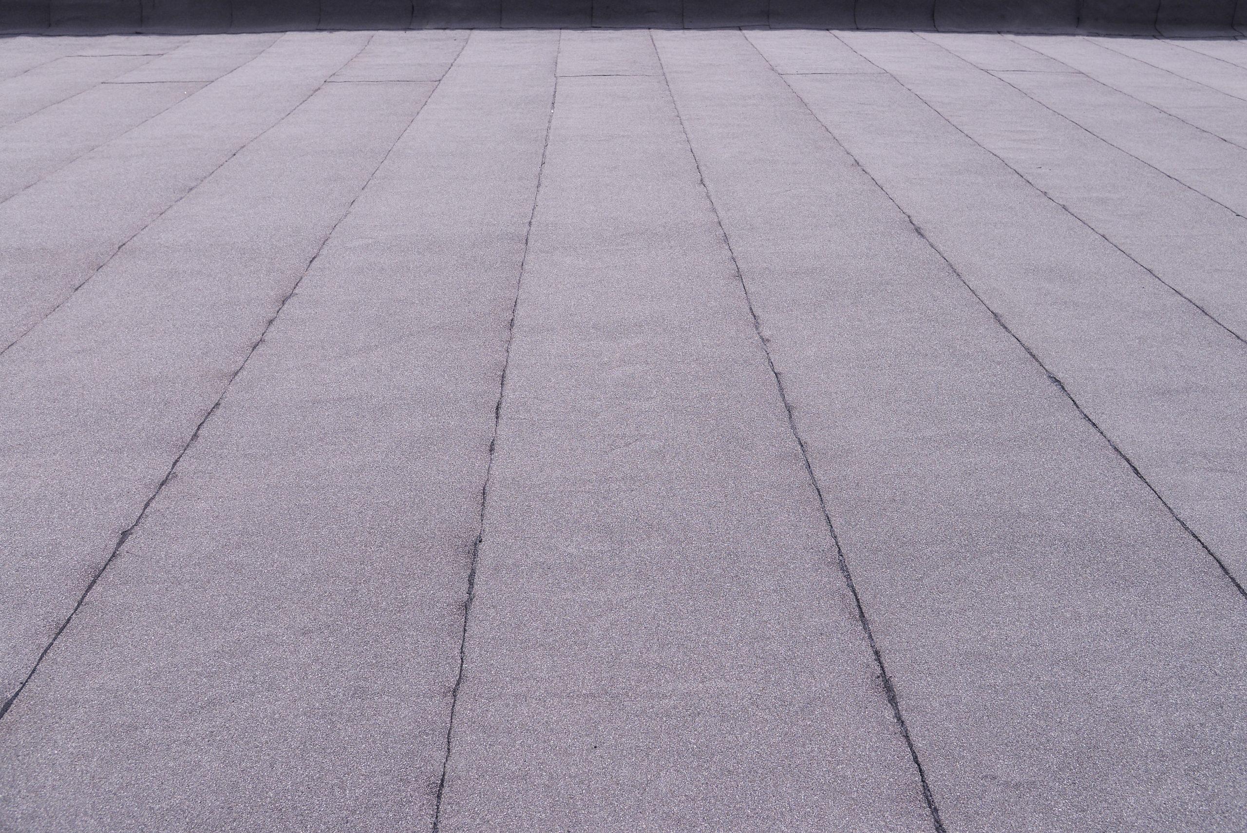 Flat surfaced roof coating. Heating and melting bitumen roofing felt background pattern